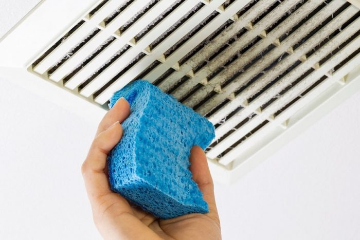 A sponge being used to clean a bathroom fan